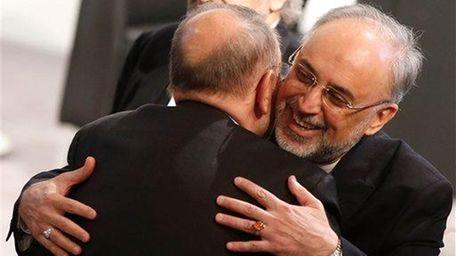Iranian Foreign Minister Ali Akbar Salehi, right, hugs
