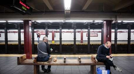 Commuters keep their social distance as they wait