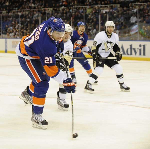 Kyle Okposo shoots the puck as Simon Despres