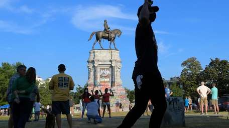 A crowd gathers near the defaced statue of