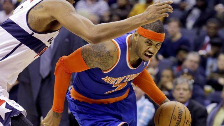 Washington Wizards forward Trevor Ariza, left, guards Carmelo