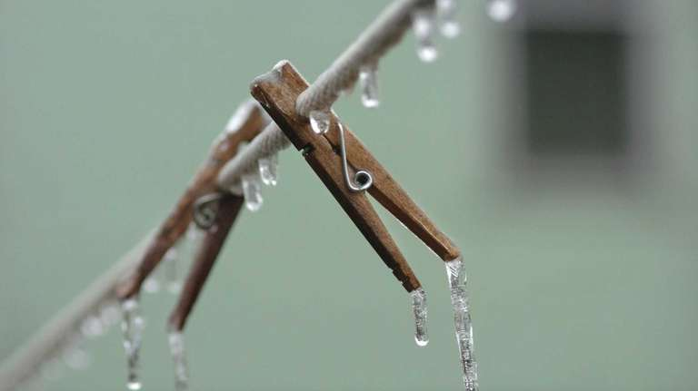 Clothes pins hang on an ice-covered wash line.
