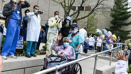 Health care workers celebrate as Barbara Holdin, of