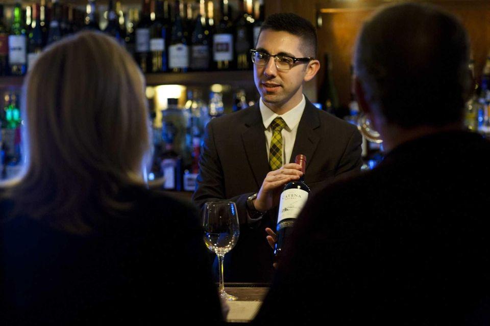 Sommelier Vincent Stilleti shows a bottle of wine