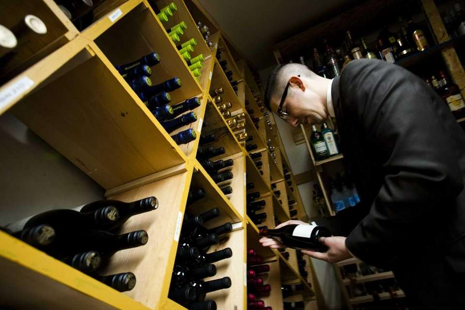Sommelier Vincent Stilleti selects a bottle from Five.Five