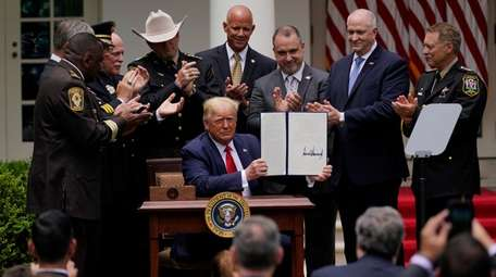 President Donald Trump signs an executive order on