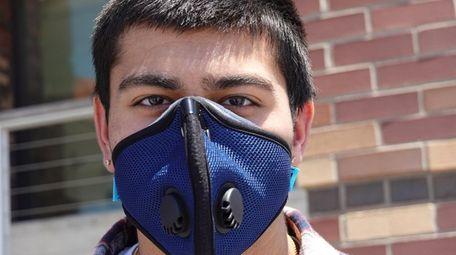Karan Kumar, 18, of Albertson, wearing his face