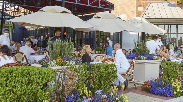 People dine outside at Bar Frites in Greenvale.