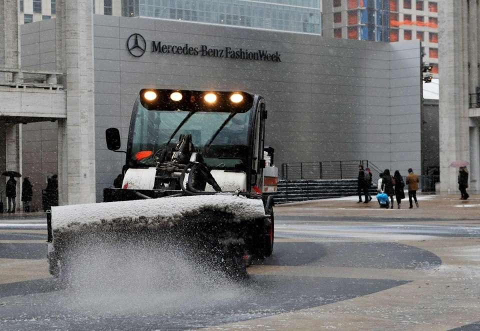 A sweeper clears snow on the plaza in