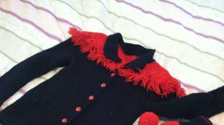 A red and navy fringed sweater and hat