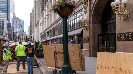 Workers remove wood panels that covered window displays