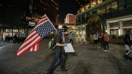 A man with an upsidedown U.S. flag walks