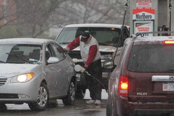 People line up for gas as the snow