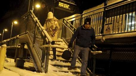 Commuters walk down snow-covered stairs at the LIRR's