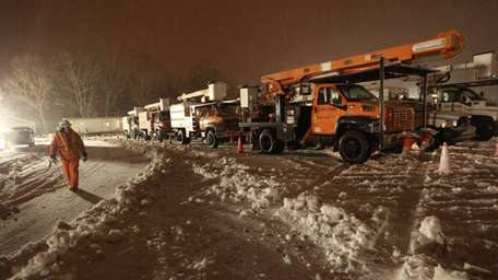Utility trucks from Ohio and Indiana wait at