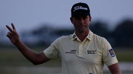Webb Simpson waves as the sun disappears on