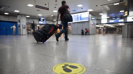 A traveler walks past a social distancing marker