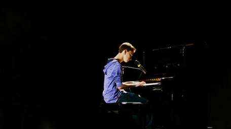 Michael Pollack, of Roslyn, plays piano during the