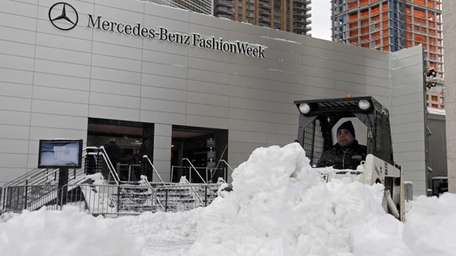 A worker plows snow from the plaza of