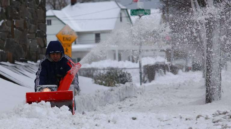 Residents clear snow on Willis Avenue in Mineola.