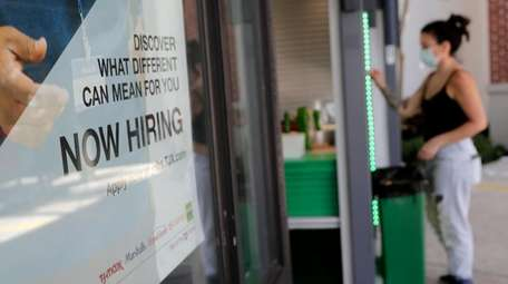"""A """"Now Hiring"""" sign is displayed during the"""