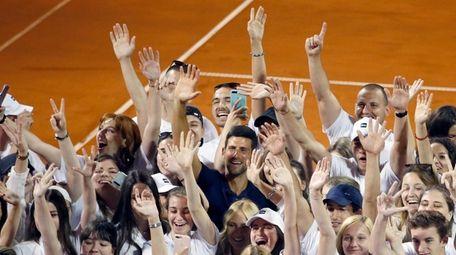 Serbia's Novak Djokovic, centre, poses with volunteers and