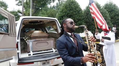 A musician plays music near the hearse carying