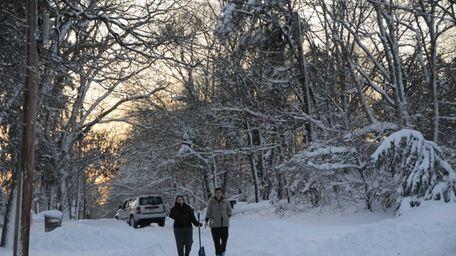 Two women walk along Greenport Avenue in Medford.