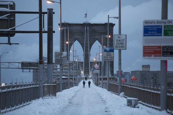 People walk along the Brooklyn Bridge following a