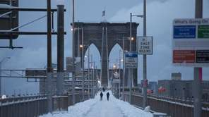 People walk along the Brooklyn Bridge following a