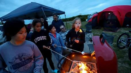 Friends gather round the campfire to roast marshmallows