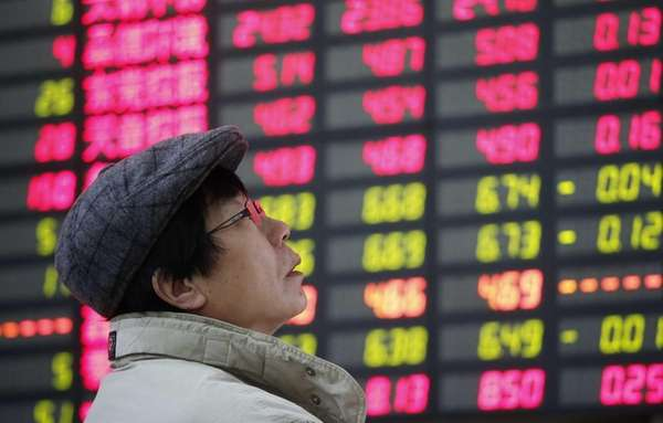 An investor looks at the stock price monitor