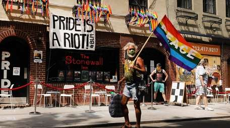 People walk by the Stonewall Inn, an iconic