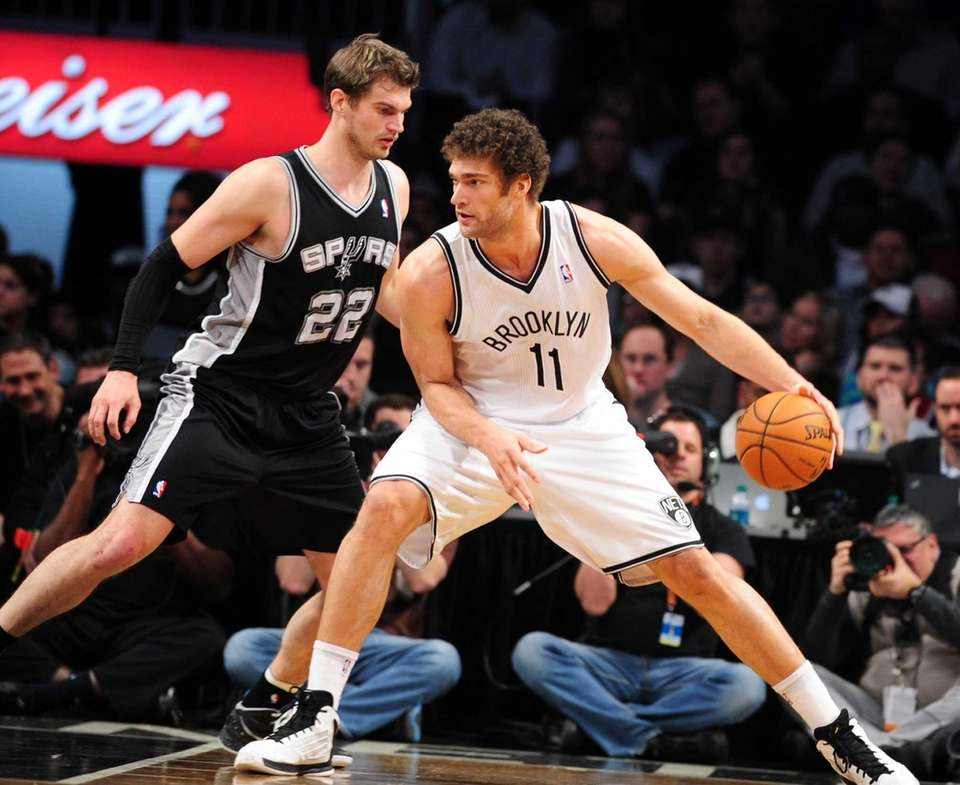 Brook Lopez is guarded closely by Tiago Splitter