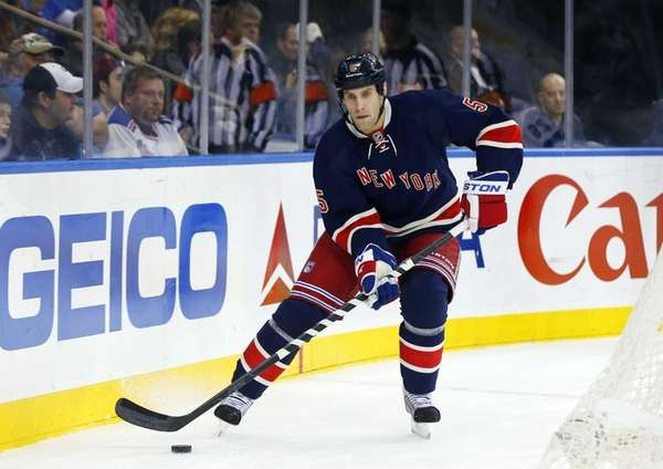 Dan Girardi skates with the puck during a