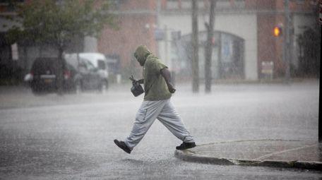 A man walks through a downpour of rain