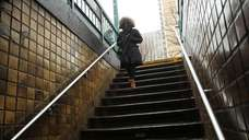 A woman enters a subway station in the