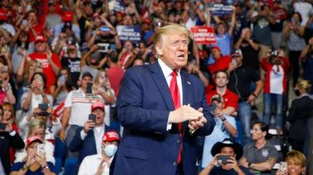 President Donald Trump claps while supporters cheer during