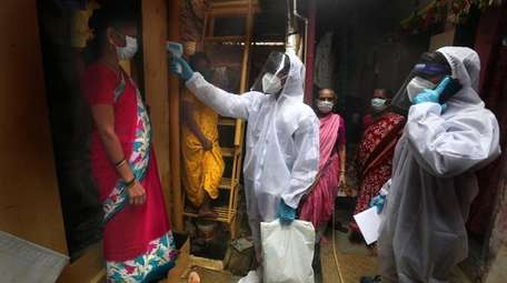 A health worker checks the temperature of a