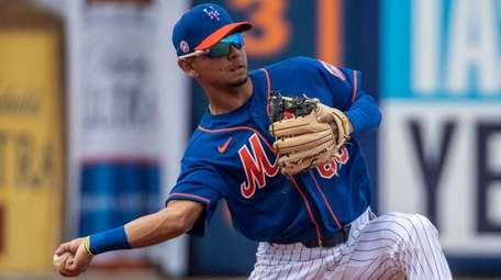 Mets' Andres Gimenez throws during a spring training