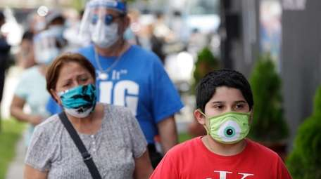 People wait in line at a mask distribution