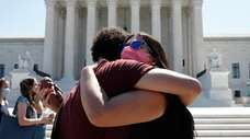 Anti-abortion protesters hug goodbye outside the Supreme Court