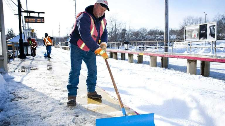 John Metzak clears the snow and ice from