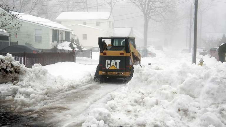 A small bobcat works to clear West 4th