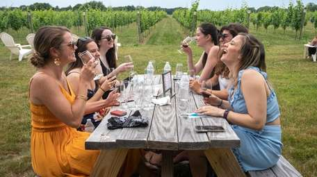 Friends taste wine at Bedell Cellars in Cutchogue