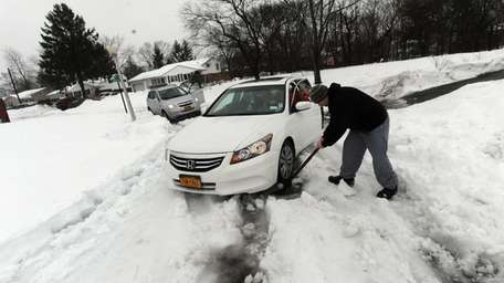 Randy Meurer of Centereach uses a shovel to