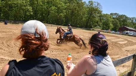 A rider circles one of the barrels while