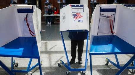 A voter fills out their ballot at a