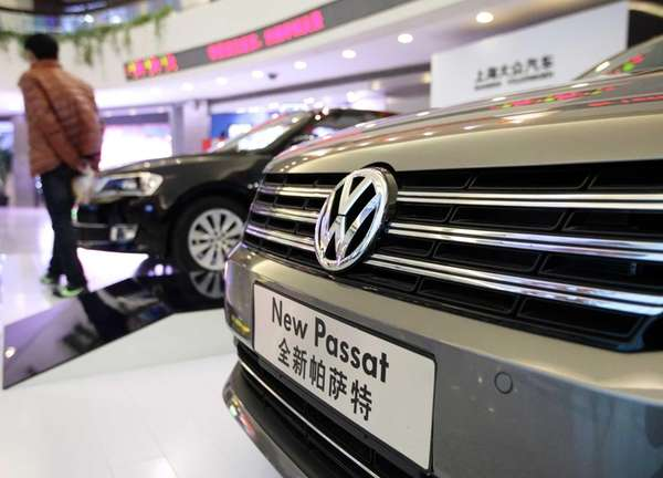 A visitor walks past Volkswagen AG Passat sedans