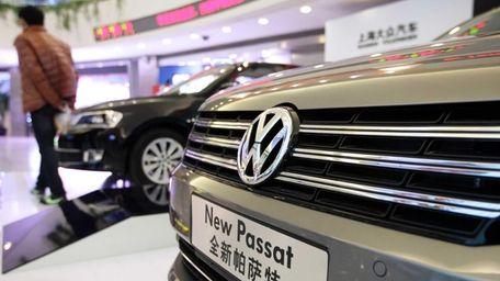 A visitor walks past Volkswagen AG Passat sedans